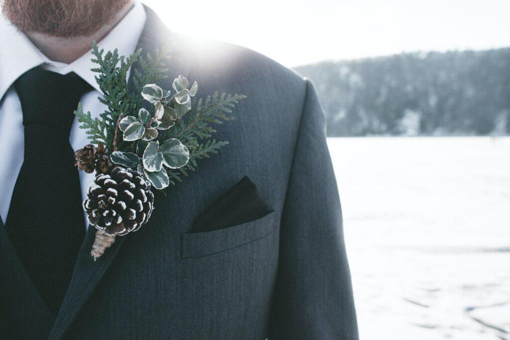 groom in a tuxedo, in winter, with pine cone decor